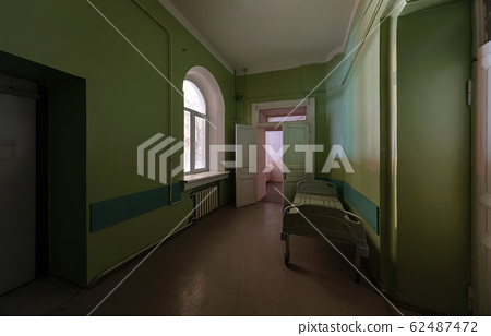 Green corridor with an empty hospital bed in an 62487472