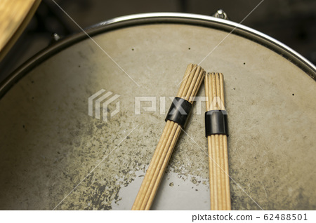 Rods of a drummer on a holed and worn snaredrum 62488501