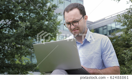 Comic emotion. Young businessman with disgusted emotion holding laptop in a park. 62488861