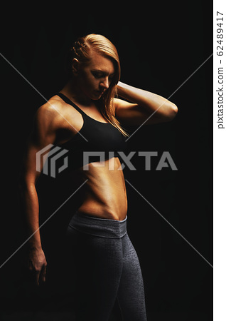 Young fit women in sports equipment, sports embossed female body, black background, hard light. Copy space, sports banner 62489417