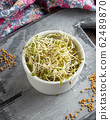 Fresh fenugreek sprouts with dry seeds in the background 62489870