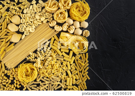 Italian pasta design template with copy space, a flat lay of many different pasta types, shot from above on a black background with a place for text 62500819