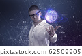 A male scientist in a white shirt holds an abstract ball in his hands against a background of plexus 62509905