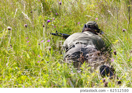 Two people playing airsoft hid in ambush behind fence 62512580