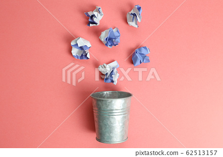 Trash can with trash on pink background 62513157