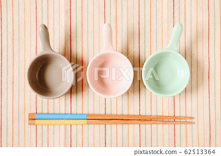 Plate and chopsticks on fabric background 62513364
