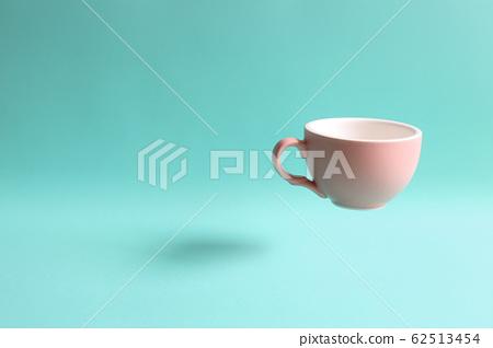 Pink mug cup floating on green background 62513454