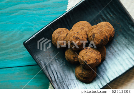 Chocolate on black plate on wooden table 62513808