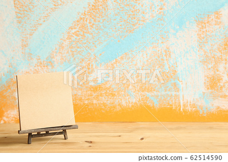 Blank canvas on wooden easel with abstract colorful painted background. Art concept 62514590