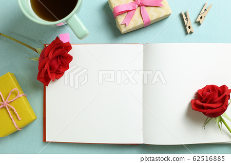 Empty note paper with red rose flower, black coffee, gift boxes on mint green background. Flat lay, top view, copy space 62516885