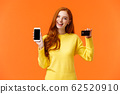 Shopping, online and finance concept. Cheerful young redhead female opened bank account, holding smartphone and credit card, smiling, recommend use online shopping application 62520910
