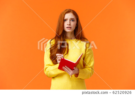 Concerned tensed attractive redhead female student cant write down everything from blackboard after lector, biting lip look troubled and perplexed, holding red notebook and pen, orange background 62520926