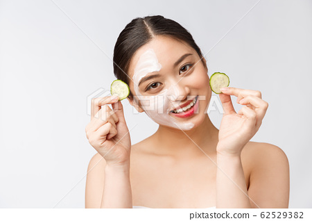 Beauty young asian women skin care image with cucumber on white background studio 62529382