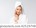 Spa skincare beauty Asian woman drying hair with towel on head after shower treatment. Beautiful multiracial young girl touching soft skin. 62529748