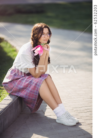 Woman with Flower Outdoors in the City Park 62532203