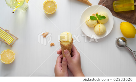 Top view of a girl holding lemon ice-cream cone 62533626