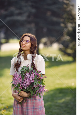Woman with Bouquet of Flowers Outdoors in the City Park 62534871