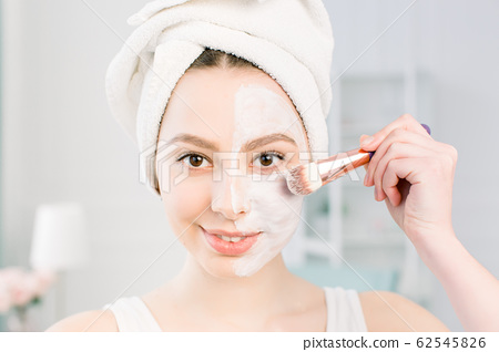 A young beautiful woman in a bathing towel after a shower and cleansing the skin applies a clay mask to the face with a cosmetic brush. beauty, health, cosmetology concept. Lifestyle. Skin care 62545826