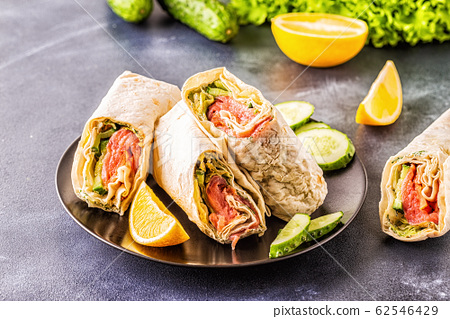 Wrapped sandwich with salmon, lettuce, cucumber 62546429