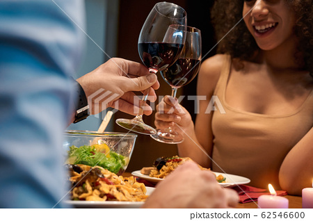 Romantic Date. Young multiethnic couple at home sitting at table eating dinner cheers with glasses of wine talking laughing joyful close-up 62546600