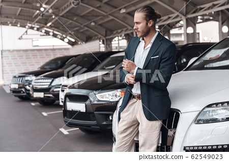 Confident young adult businessman standing near car on parking 62549023