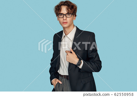Freestyle. Young businessman in suit and glasses with digital watch standing isolated on gray posing relaxed 62550958