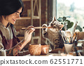 Craftsperson Concept. Young tattooed woman with piercing making pottery at creative studio sitting near window holding brush playing with cat laughing playful 62551771
