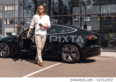 Young adult man standing near car with smartphone 62552092