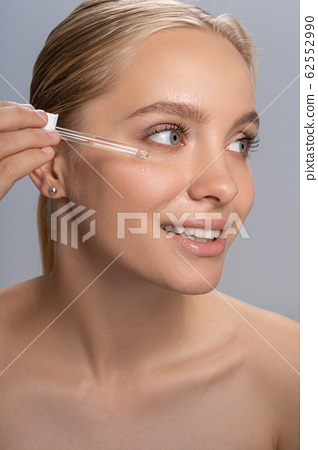 Attractive young woman testing serum for skin moisturizing 62552990