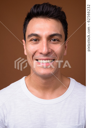 Young handsome Hispanic man against brown background 62566232