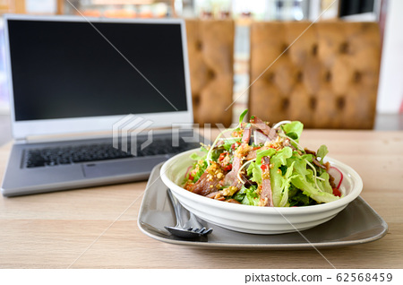Modern laptop with spicy pork salad on table 62568459
