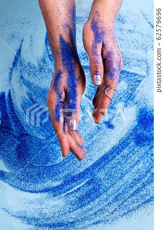 Abstract blue glitter sparkle background with woman hand. Beauty art concept 62579696
