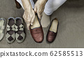 Elderly woman putting on shoes 62585513