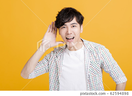 young man  with hand over ear listening and 62594898
