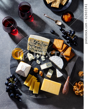 Cheese assortment on marble cutting board with wine. Grey background. Top view. 62603341