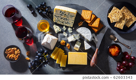Cheese assortment on dark marble cutting board with red wine. Grey background. Top view. 62603343