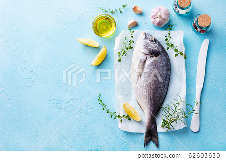 Raw Dorado fish with cooking ingradients. Blue stone background. Top view. Copy space. 62603630