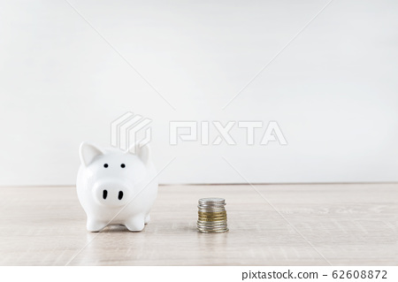 White pig money box and stack of coins  62608872