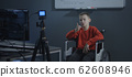 Boy in wheelchair recording a video for vlog 62608946