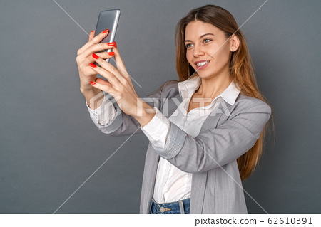 Young business woman studio isolated on gray taking selfie photos 62610391