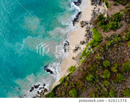 Aerial view of sand beach with rocks and green cliff, Bali 62621378