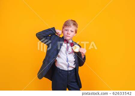 Pretty small boy in black suit with gold medal on his neck over yellow background 62633542