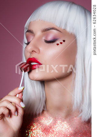 Beauty Glamour model woman with trendy white hair style and creative makeup holding red sweet lollipop candy 62634028