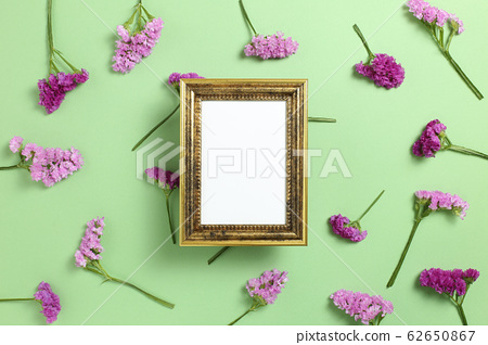 Antique photo frame with pink purple statice flowers on green background. Floral composition, flat lay, top view, copy space 62650867