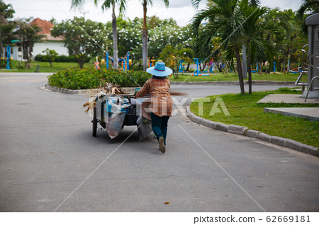 Road sweeper worker cleaning city street. 62669181
