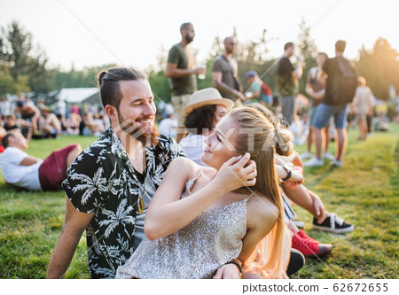 A young couple at summer festival, talking. 62672655