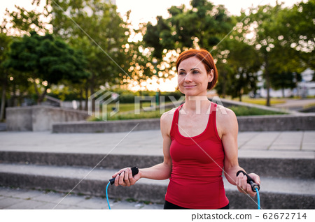 Young woman doing exercise outdoors in city with skipping rope. 62672714