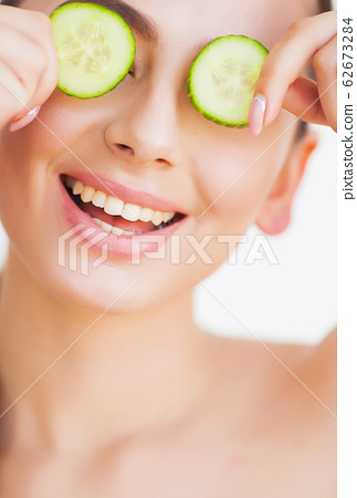 Beautiful young woman with cucumbers on eyes. 62673284