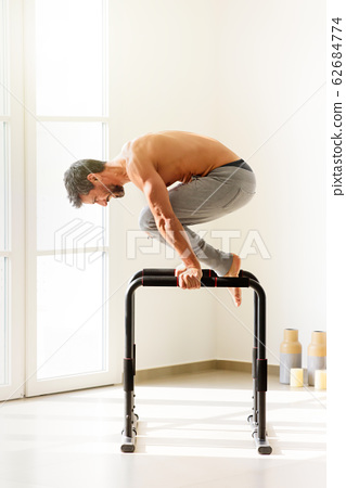Side view of a man doing planche exercise 62684774