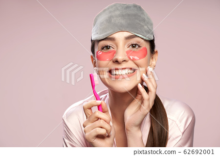 Cheerful young woman with under-eyes patches holding toothbrush 62692001